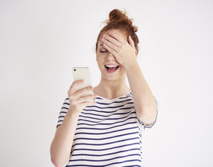Girl using mobile phone and laughing at studio shot