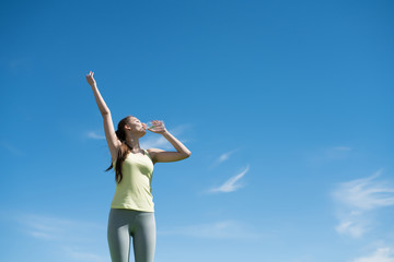 active slender girl drinks water after a difficult workout, under a blue sky