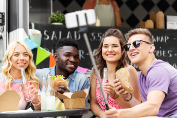 leisure, technology and people concept - happy young friends with food and non alcoholic drinks and taking selfie at food truck