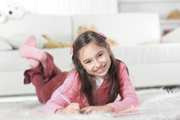 close up.little girl draws lying on the floor in the room