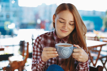 Young woman looking to a cup of coffee smiling