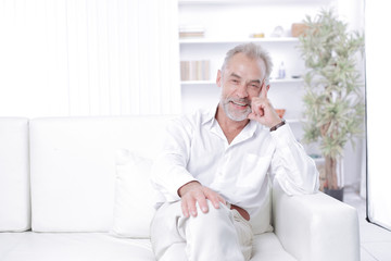 cheerful senior businessman sitting on the couch in the office