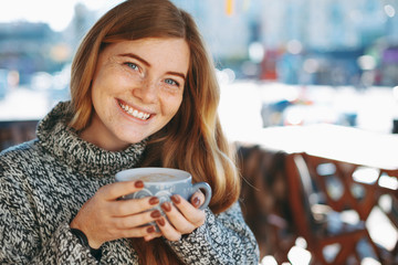 Close-up of natural reddish girl holding a big cup of coffee sho