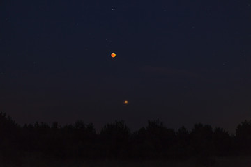 Night sky over forest, visible full eclispse of Moon, Mars in perigee