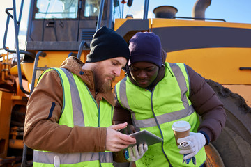 Waist up portrait of two workers, one African-American, drinking coffee and using digital tablet standing next to heavy industrial truck on worksite, copy space
