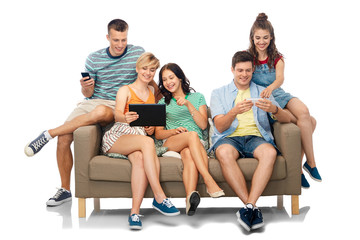 friendship, leisure and technology concept - group of happy smiling friends with tablet pc computer and smartphones sitting on sofa over white background