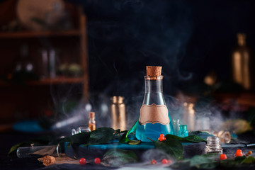 Blank label on a magic potion bottle. Modern witchcraft concept with potions, berries, herbs and occult equipment. Magical still life with copy space on a dark background.