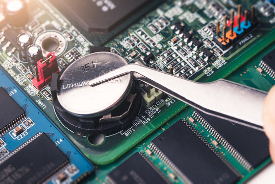 The technician is laying a cr2025 battery on the socket of the computer motherboard. the concept of computer, service, electronics, hardware, repairing, upgrade and technology.