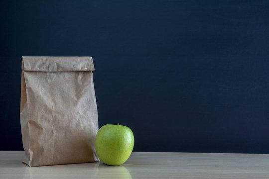 Bolsa de almuerzo de papel en el  pupitre de la escuela con una manzana verde