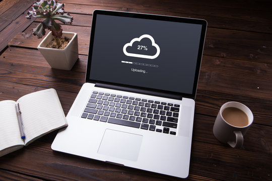 Cloud upload processing data on laptop with internet with office equipment and wooden desk background