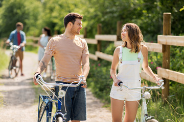 people, leisure and lifestyle concept - happy young couple with fixed gear bicycles on country road in summer