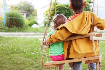 children sitting on a swing in the garden. older brother hugging little sister