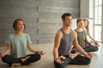 Young handsome male yoga teacher showing lotus pose to three female pupils, practicing yoga in gym. Fitness, sport, training and yoga lifestyle concept.