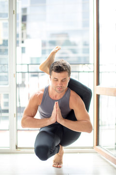 Athletic caucasian muscular young man in sportive wear working out at home against big window, yoga, pilates, fitness training.