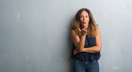 Middle age hispanic woman standing over grey grunge wall looking at the camera blowing a kiss with hand on air being lovely and sexy. Love expression.