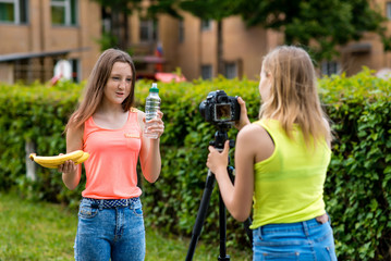 Two girls girlfriends, in the summer in the city. Record video on the camera. In the hands holding a banana bottle of water. The concept of healthy eating. Use camera with tripod.