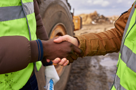 Mid section  portrait of two unrecognizable industrial workers wearing reflective jackets shaking hands outdoors