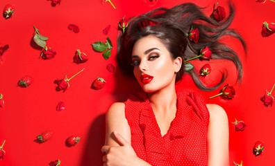 Wall Mural - Beauty sexy model girl lying on red background with rose flowers and strawberries. Beautiful brunette young woman with long hair and perfect make-up, red seductive lips, smoky eyes. Trendy makeup