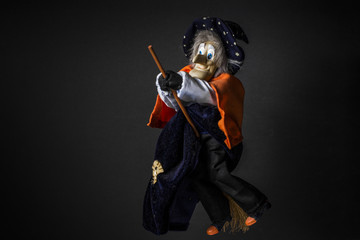 Halloween witch doll isolated on a black background. Halloween decor toy. Closeup