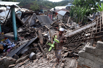 A man carries a small bicycle through the ruins of houses damaged by an earthquake in West Lombok,