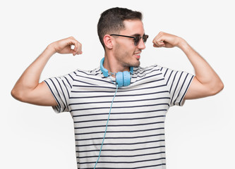 Handsome young man wearing headphones showing arms muscles smiling proud. Fitness concept.
