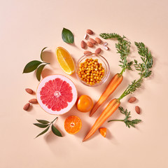 Natural organic citrus fruits, carrots, sea buckthorn berries - ingredients for making homemade detox smoothie on yellow paper background.