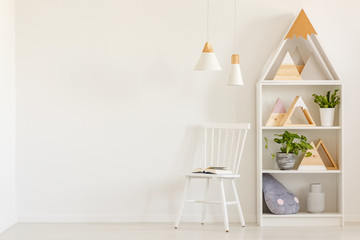 Triangles on shelves in scandi kid's room interior with white chair against the wall with copy space. Real photo