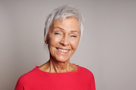 happy smiling mature woman in her sixties with trendy white short hair