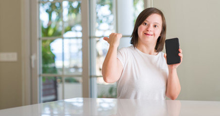 Down syndrome woman at home using smartphone pointing and showing with thumb up to the side with happy face smiling