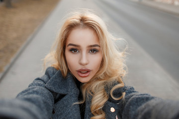 Stylish fashionable woman with big lips makes selfie on the street