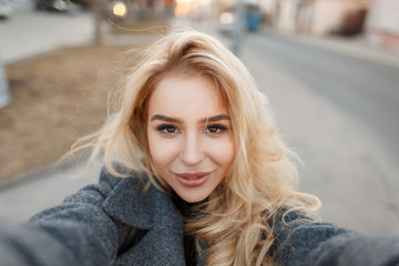 Young stylish woman in gray coat makes selfie