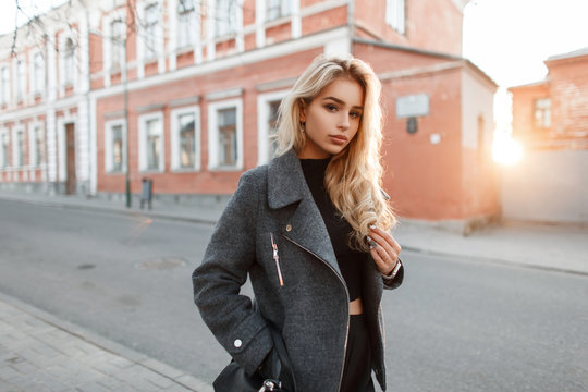 Stylish beautiful young model woman with a bag in a fashionable jacket in the city at sunset