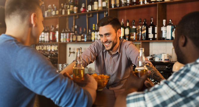 Men drinking beer and communicating with bartender