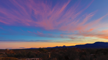Spectacular sunrise in the Kagga Kamma Nature Reserve in South Africa with pink streaky clouds in the sky