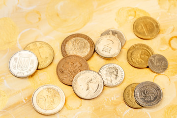 Coins of different countries on an abstract golden background