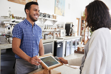 Male barista smiles at a female customer in a coffee shop
