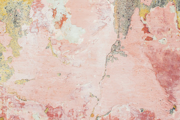 Old colored cracked wall. Grunge wall texture for design. Colored cracked background. Old paint texture is chipping and cracked fall destruction. Background of old pink painted wall.