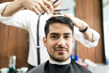 Confident Man Getting Hair Styled By Hairdresser In Salon