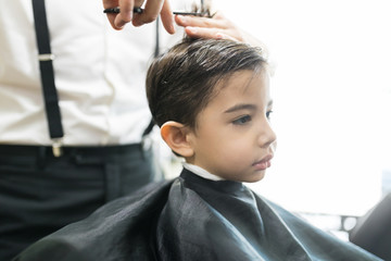 Little Client Is Getting Haircut By Hairdresser At Barber Shop
