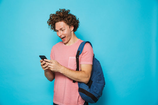 Photo of handsome college guy with curly hair wearing casual clothing and backpack smiling and holding smartphone, isolated over blue background
