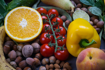 Healthy food background, frame of organic food. Ingredients for healthy cooking: vegetables, fruits, nuts, spices. Balanced diet food on a dark black background. Close-up.