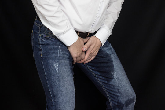 The man holds his hands to the crotch, groin, wet pants and incontinence, prostatitis