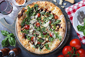 Pizza with arugula, tomato and parmesan