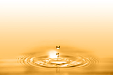 Closeup on drop of cosmetic golden oil liquid creating a circular wave. Wall mural