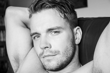 Hunky muscular, sexy shirtless man with muscules and pecs sitting on sofa, looking at camera
