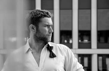 Handsome hunky man with unbuttoned shirt and loose bowtie stands on hotel balcony with sckyscraper backdrop