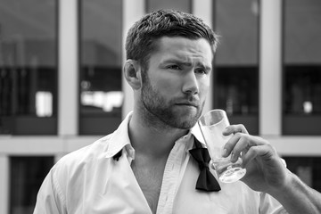 Handsome hunky man in tuxedo, unbuttoned shirt and tie stands on hotel balcony, drinking a beverage