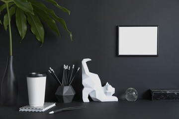 Black design room with mock up poster frame, cat figures, tropical leaf and office accessories. Modern and stylish black interior.