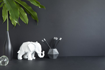 Black design room with copy space , elephant figures, tropical leaf and photo accessories. Modern and stylish black interior.