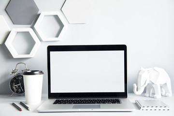 Modern and design workspace with laptop mock up screen, office accessories , elephant figures and cup of coffee. Gray interior with hanging hexagone shapes. Design space for freelancer.